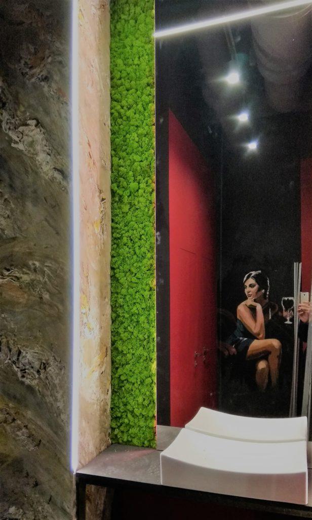 Вставка из стабилизированного мха за зеркалом возле раковины. Озеленение ресторана